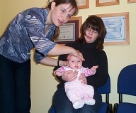 Alison treating a baby using CranioSacral Therapy while mother assists